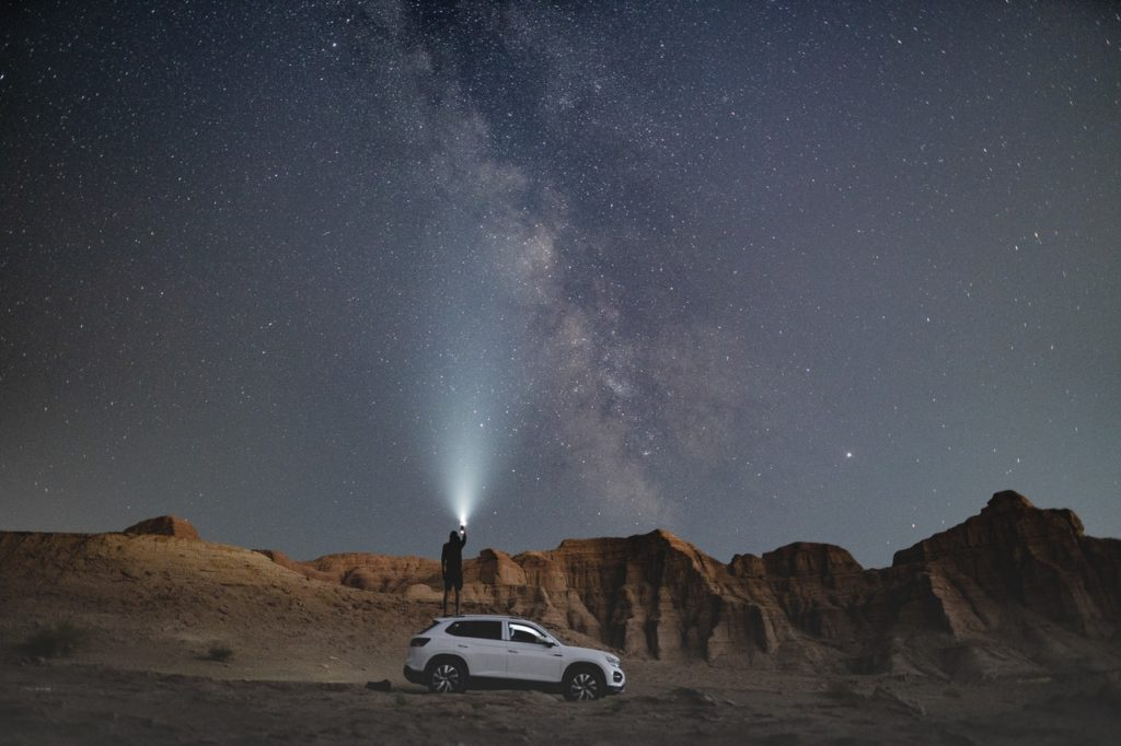 an SUV going under the milky way